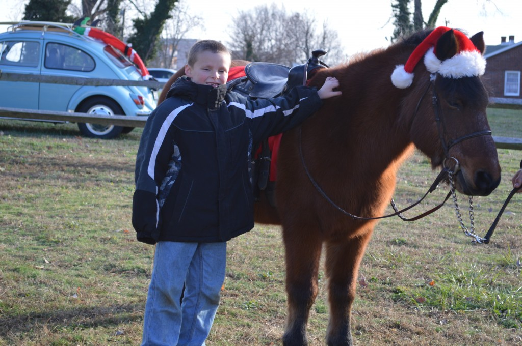 Boy and a beautiful pony in a santa hat