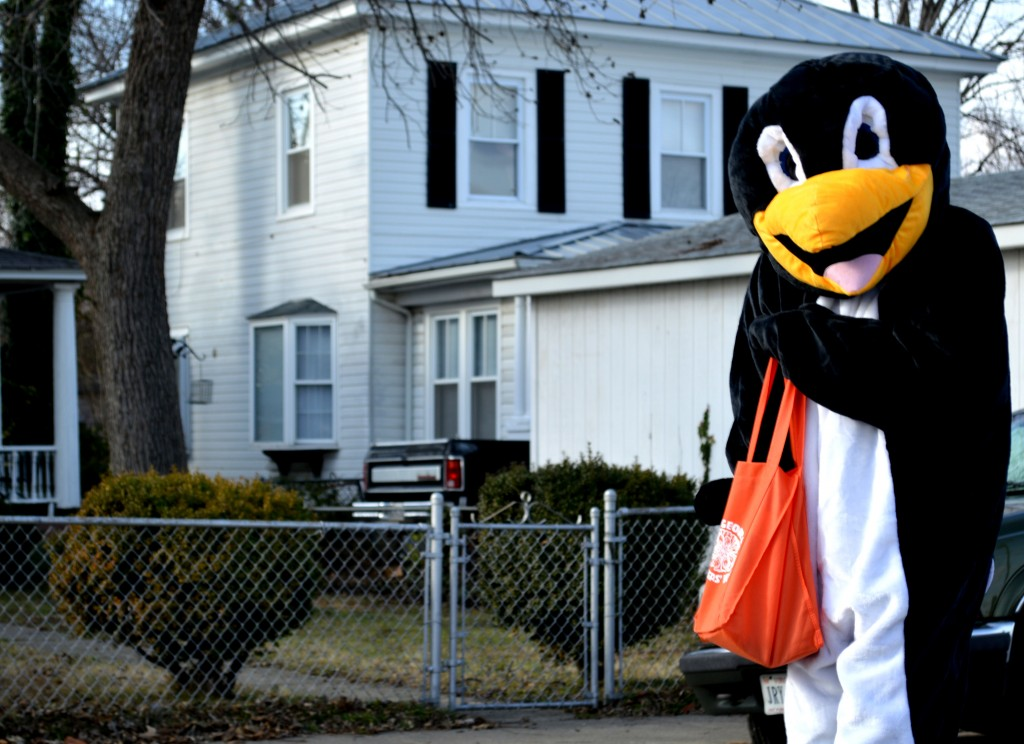 A man in a penguin suit in a Christmas parade