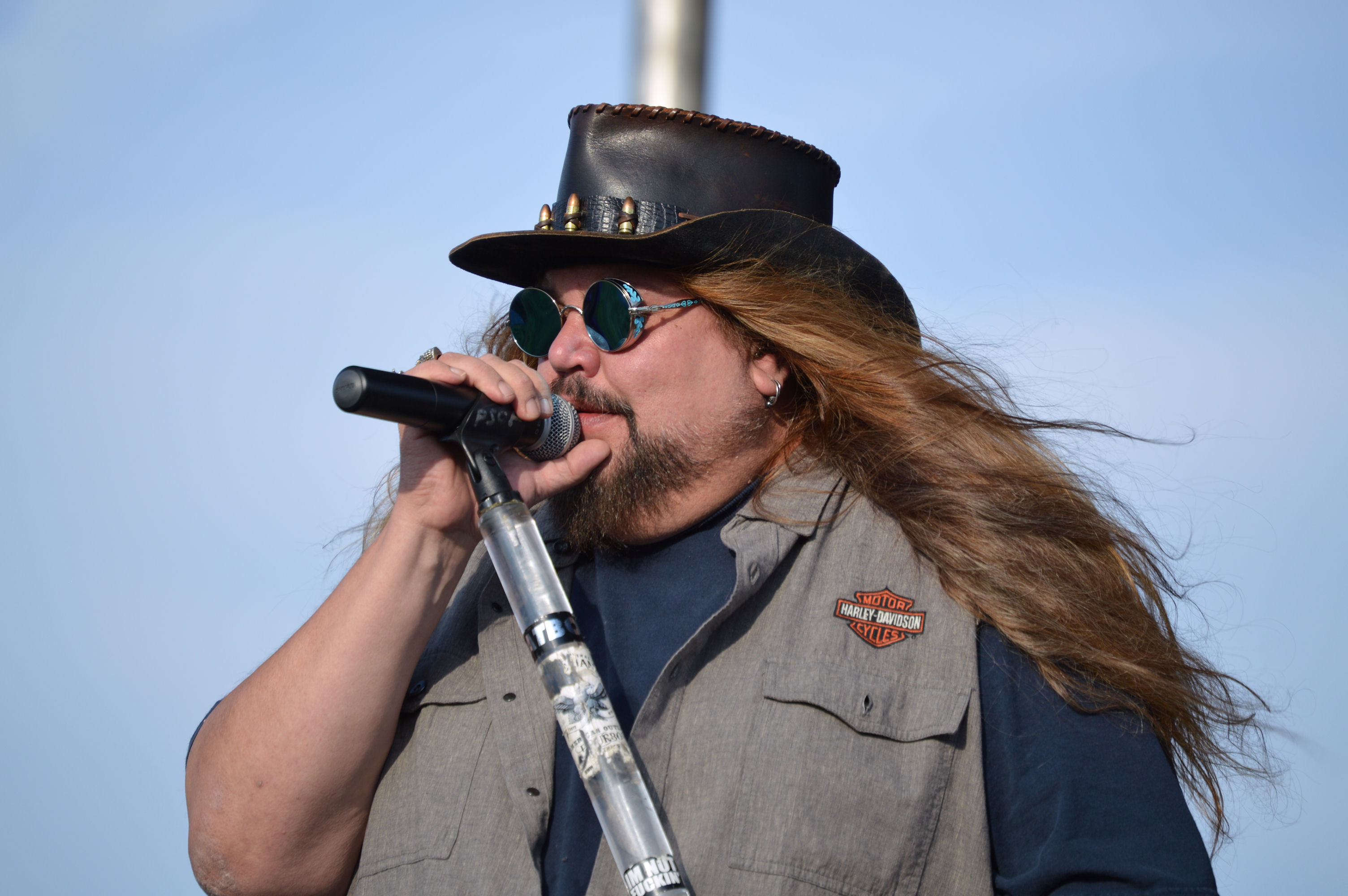 A large man with long blonde hair and a leather hat on sings into a microphone on an acrylic, clear stand