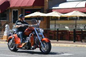 A white man sits on an orange motorcycle in front of a diner car