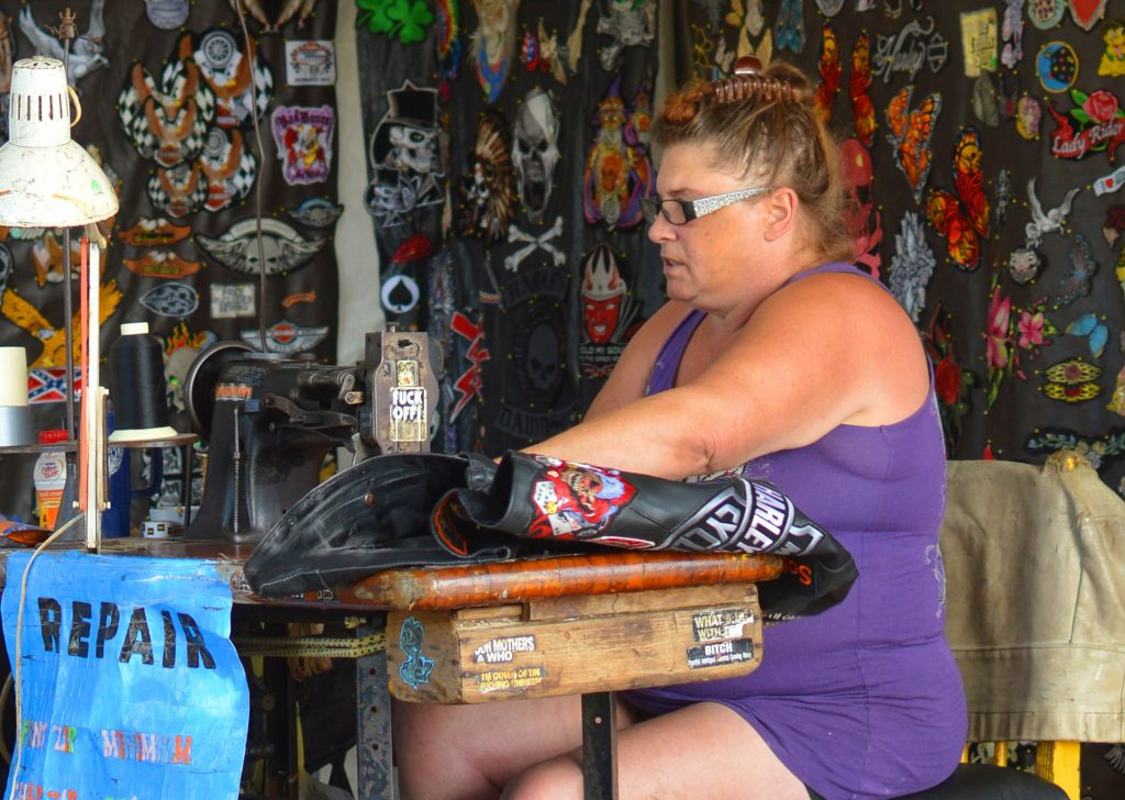 a white woman in a purple tanktop sits at a sewing machine surrounded by patches.