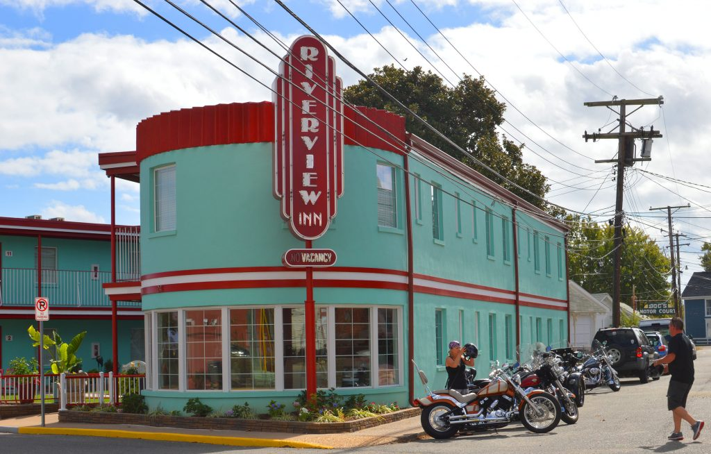 Motorcycles line the street beside a blue-green and red Art Deco 1940s era motel
