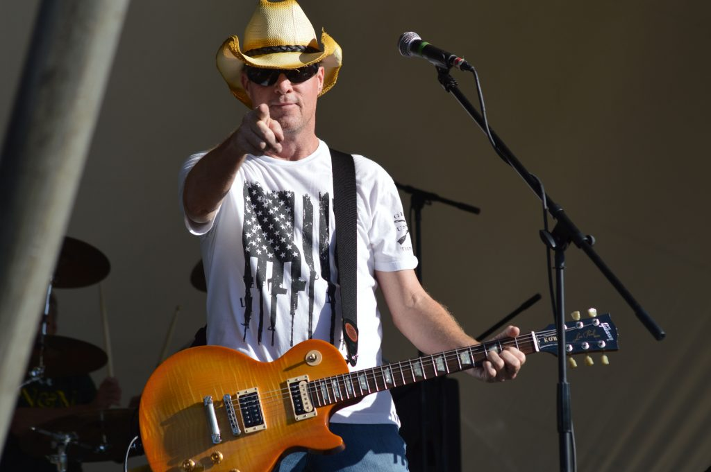 A white man wearing a cowboy hat and holding a guitar points at the camera