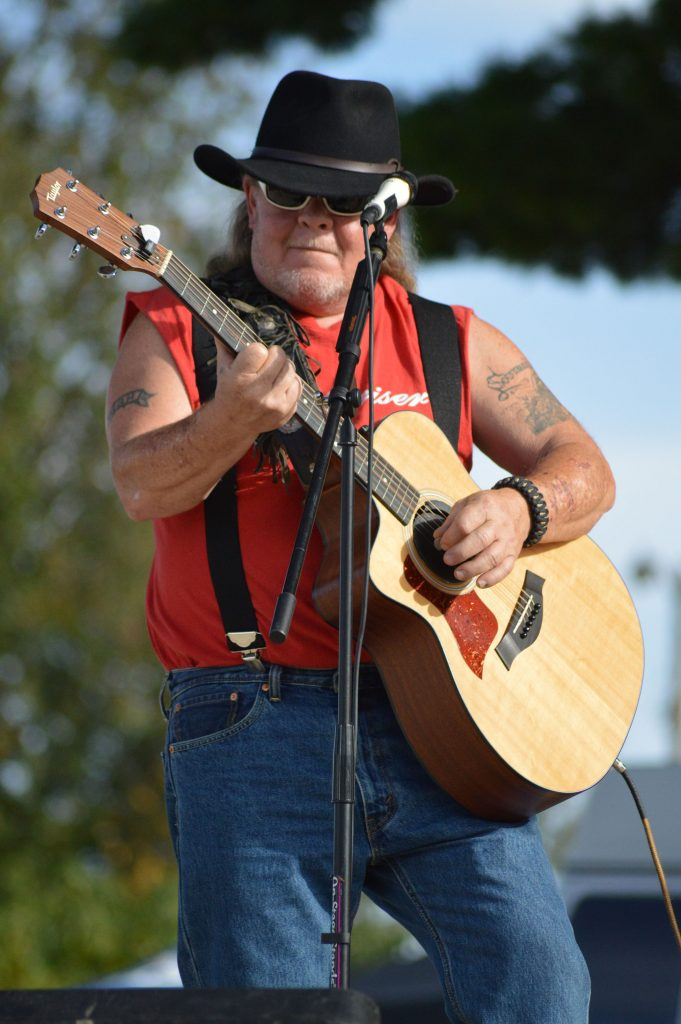A white man in a cowboy hat plays an acustic guitar. He is wearing a red shirt and black suspenders.