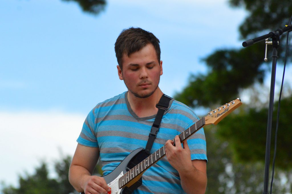 A young man with short dark hair plays the guitar.