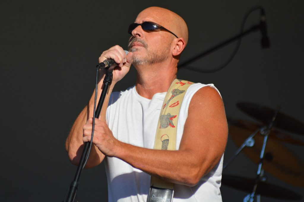 A bald white man stands in front of a microphone.