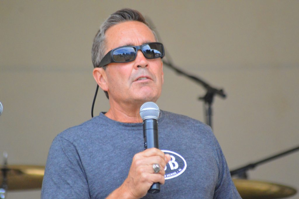 A white man, very cleancut, wearing sunglasses adn a grey shirt holds a microphone.