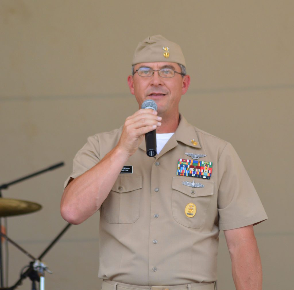 A white man in khaki naval uniform and glasses holds a microphone