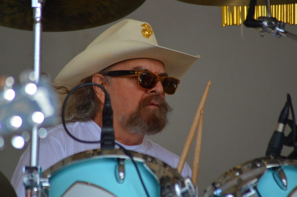 A white man with full beard and long greying hair in a cowboy hat and sunglasses plays the drums.
