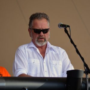 a white man in sunglasses with short salt and pepper hair plays the keyboard