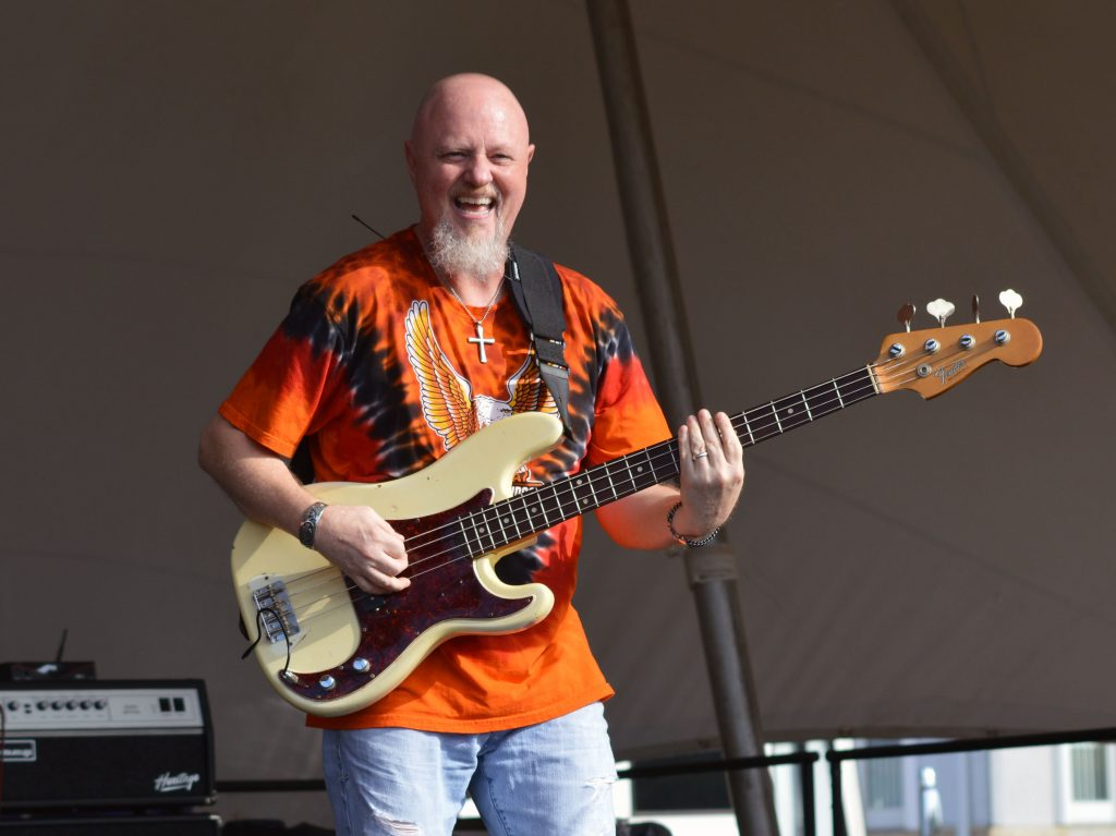 A white man, bald, but with a grey beard plays the bass in a bright orange shirt