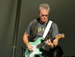 A white man with greying hair plays the guitar