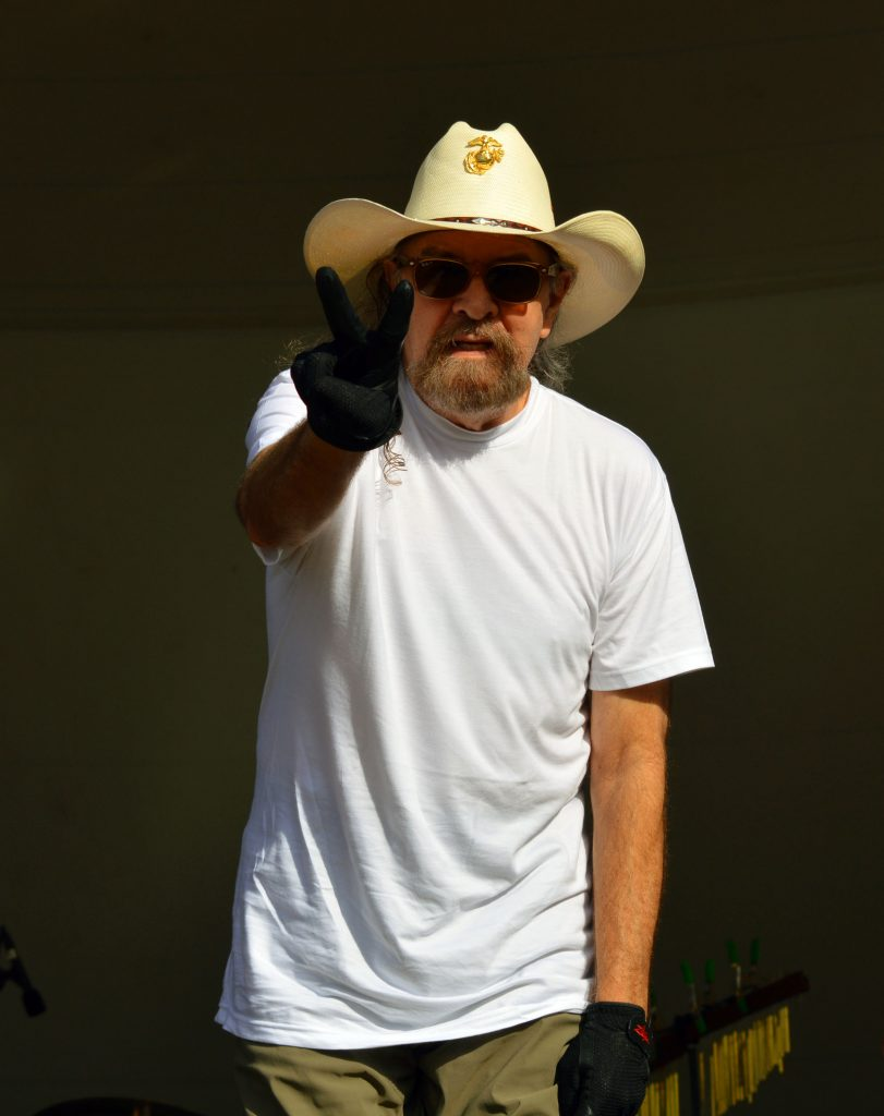 A white man with long hair, a beard and cowboy hat gives the peace sign.