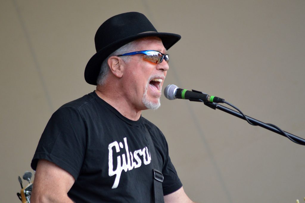 A white man with grey hair and black hat sings into a microphone