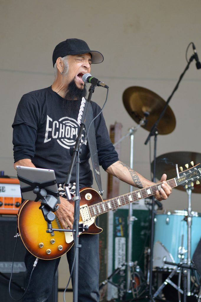 A white man with a black goatee and grey hair holds a guitar and sings into a microphone
