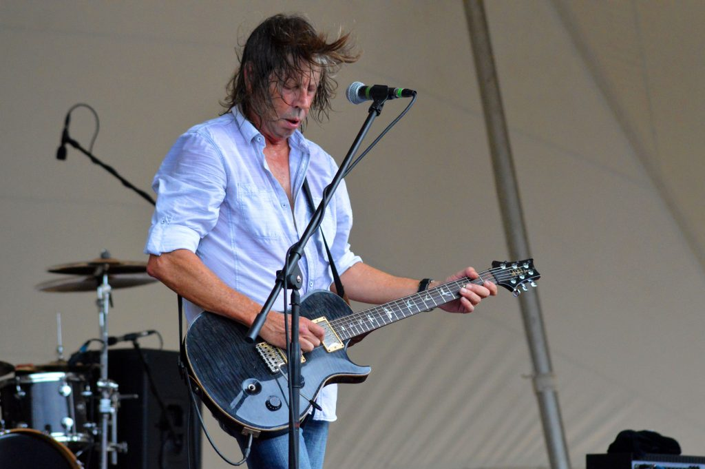 a white man with hair flying in the wind plays guitar.